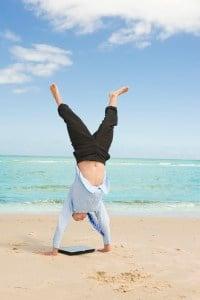 businessman doing handstand on the beach